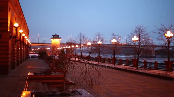 Embankment with lanterns and bridge with cars on winter evening