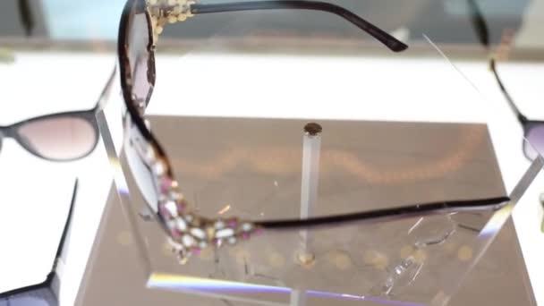 35f65b042e Όμορφα Μοντέρνα Γυαλιά Στρας Στροβιλίζονται Πίσω Από Γυαλί Στο Κατάστημα —  Αρχείο Βίντεο