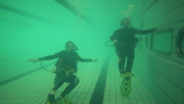 Zwei Taucher mit Sauerstofftanks trainieren unter Wasser im Pool
