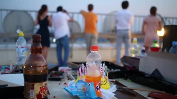 Moskva - 8 srpna 2015: Tabulka s nápoji a potravinami před rodinou a sousedy díval ze střechy na narozeninovou oslavu. Na den narození tradice sfoukne svíčky na dort a dělat si