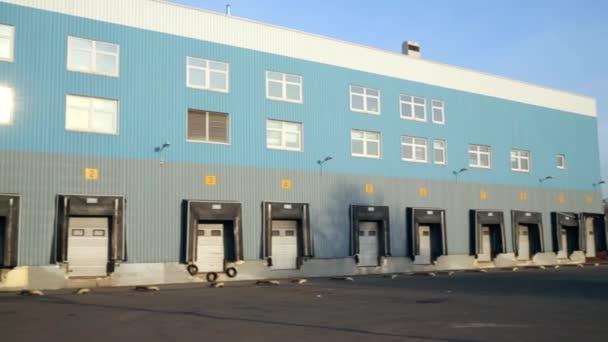 dreifarbiges Gebäude mit mehreren Türen entlang der Fassade.