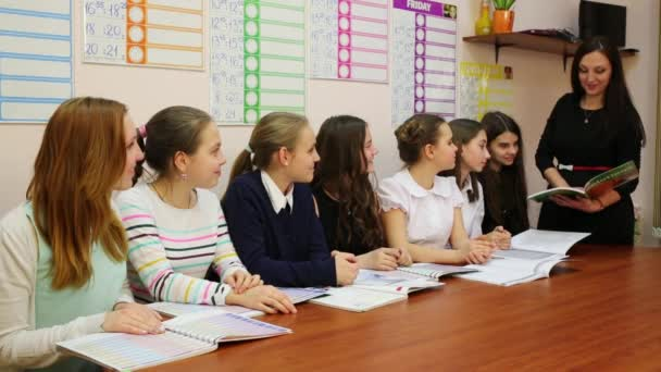 Seven girls listen to the teacher, who is standing next to the table with the textbook in hands