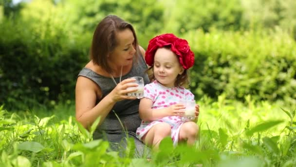 Little cute girl in flower wreath and her mother drink milk