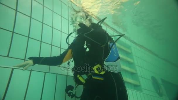 moskau - 11. apr 2015: Mädchen und Frau in Neoprenanzügen camaro unter Wasser mit Taucherbrille. Firma camaro - mehr als 40 Jahre auf dem Markt für Tauchausrüstung und Tauchausrüstung
