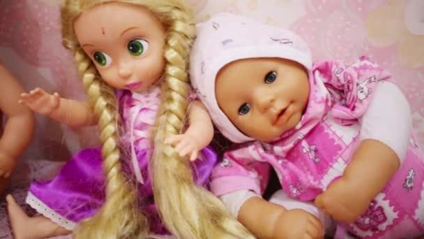 Tři krásné hračky panenky na poličce v pokoji dětí