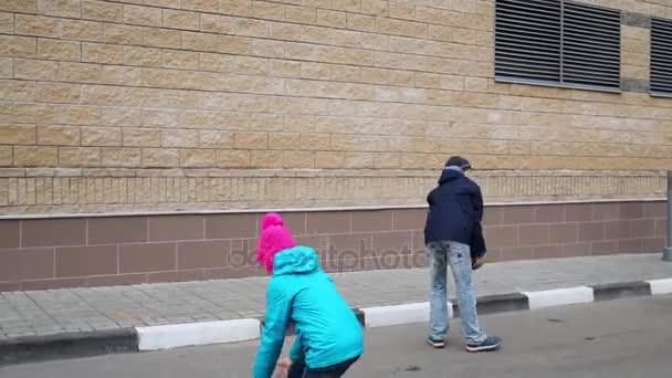 Zadní chlapec a dívka si hraje s míčky zdi venkovní
