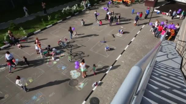 Top view of children drawing on pavement and kids with balloons