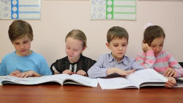 Čtyři děti sedět u stolu, čte knihu a otáčejte stránky