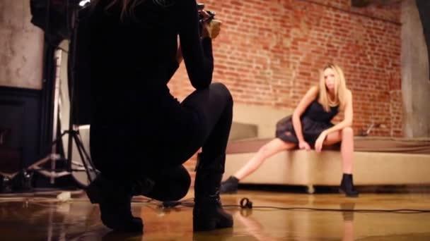 Zadní část natáčení fotograf a pózuje modelka v zaměření ve studiu