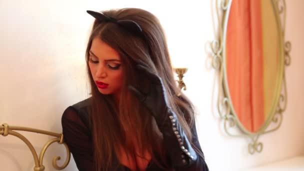 Katze im Lederkostüm posiert neben Spiegel im Schlafzimmer