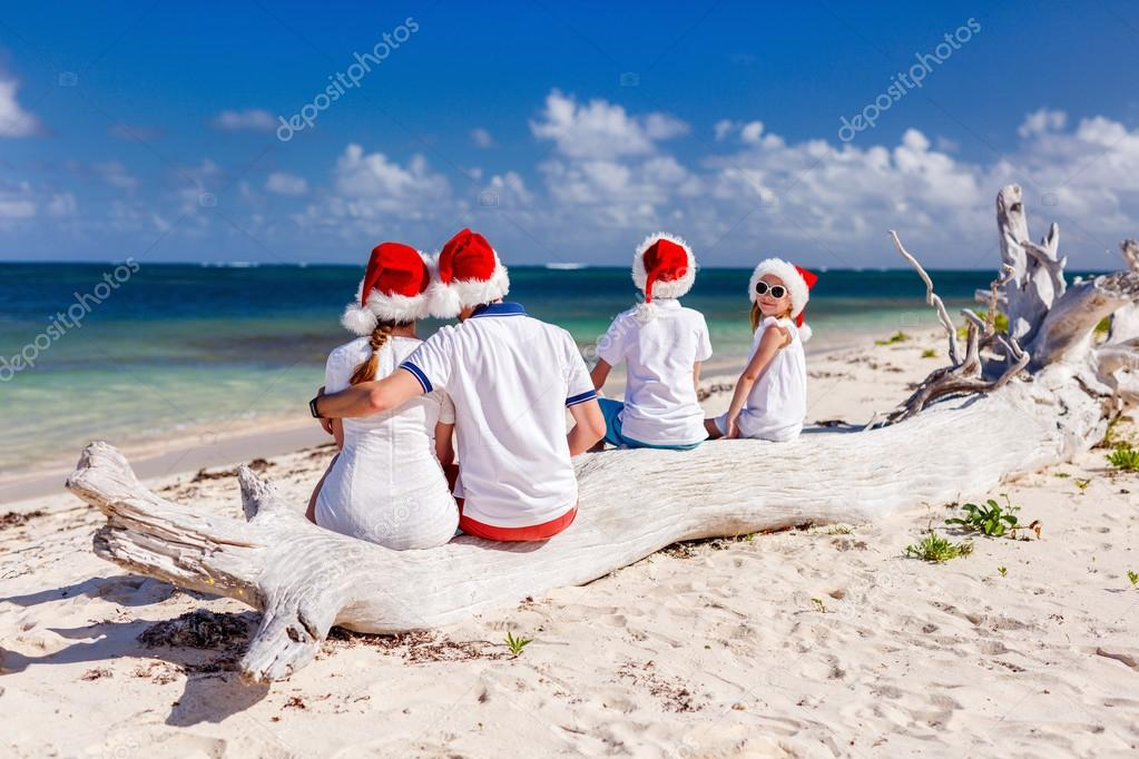 fe3e082f10e5 Πίσω όψη του όμορφη οικογένεια φορώντας κόκκινα καπέλα Santa στο τροπικό  beach γιορτάζει τα Χριστούγεννα — Εικόνα από ...