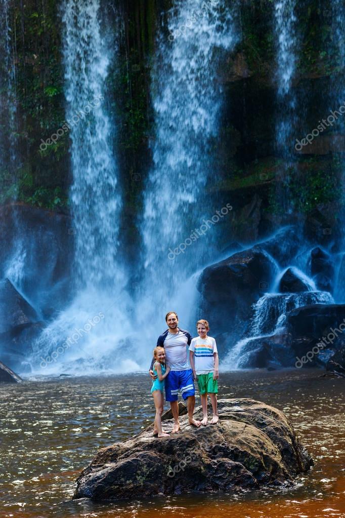 Family swimming in waterfall