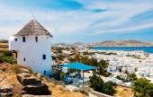 Fotografie White greek windmill overlooking traditional village on Mykonos Island, Greece, Europe
