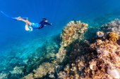 Underwater photo of a young man snorkeling free diving at coral reef in tropical ocean