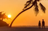 Fotografie Silhouettes of two kids at tropical beach during sunset