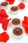 Rosenblätter und brennende Kerzen