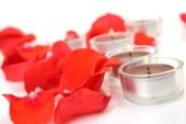 Fotografie rote Blütenblätter und brennende Kerzen