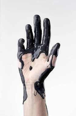 female hand in black oil