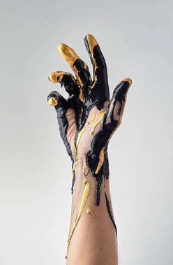 Female hand in liquid black and golden oil