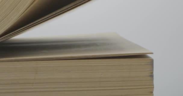 Otočení stránky staré knihy se zažloutlými stránkami a černou obálkou
