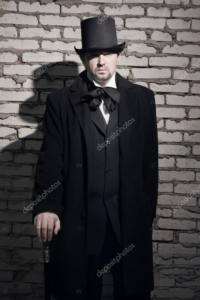 victorian man in the black coat top hat and in a tie