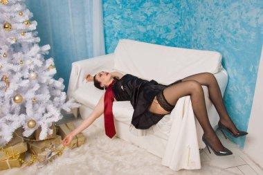 Strangled beautiful woman in black dress lies near the Christmas