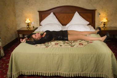 Strangled beautiful woman in a black dress lies on a bed. Simula