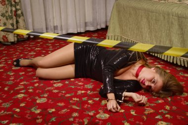 Strangled beautiful woman in a black dress lies on the floor. Si