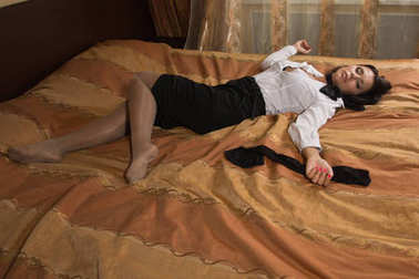 Strangled beautiful business woman in a bedroom.