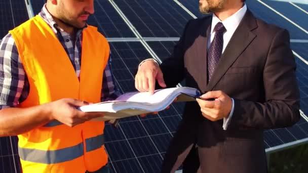 Na záběry inženýr a podnikatel diskuse technické výkresy, solární panely za nimi