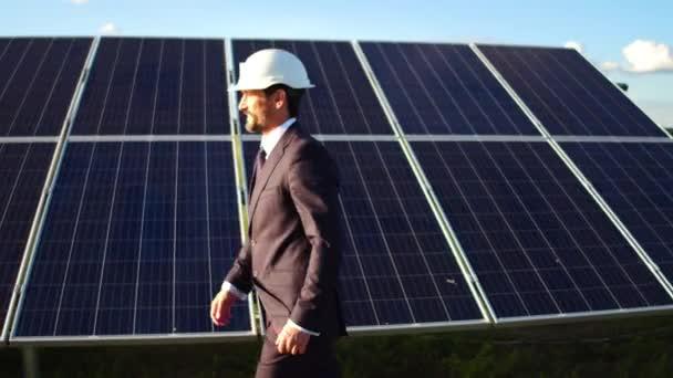 Pohled na podnikatel chodit po solárních panelů instalovaných v poli