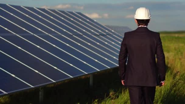 Pohled zezadu na člověka v oblasti, kde jsou nainstalovány solární panely