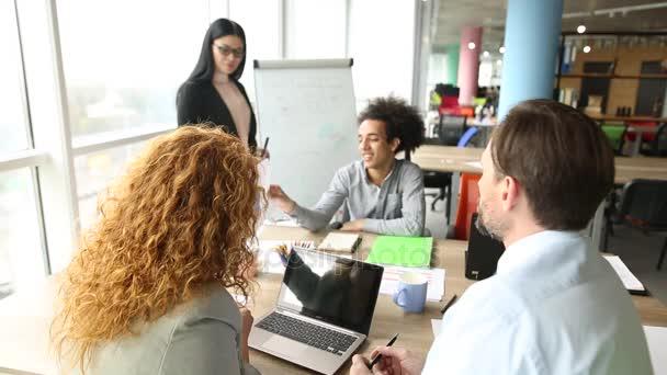 Obchodní tým pracující na diagramu v moderní kanceláři