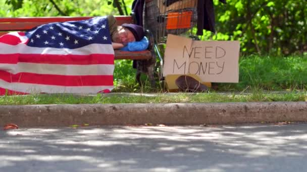 Tramp lying on bench using USA flag as blanket.