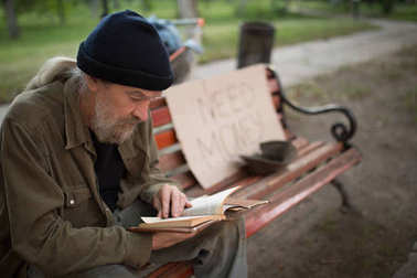 Close up view of old man reading while sitting on bench.