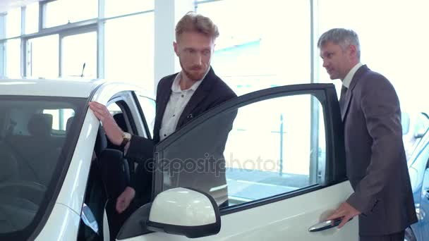 Auto showroom, sales manager showing new car to young man.