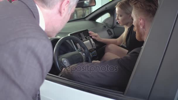 Šťastný pár sedí v nové auto, okukovala, vozidlo prodejce zobrazeno vůz kupujícím