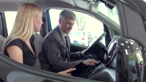 Vehicle dealer showing car to young pretty woman.