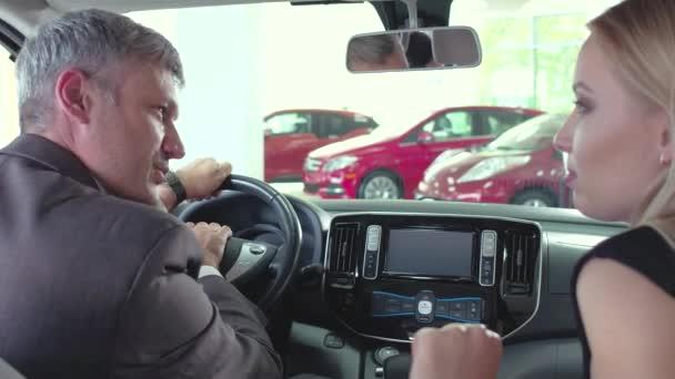 Autosalon auto, prodejce vozu a zákazník sedět na předních sedadlech, testování nové auto