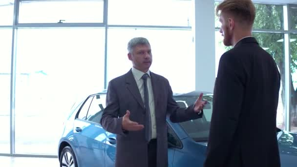 Pohledný muž na showroomu auto s prodejci vozu