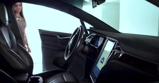 Young woman is going to sit behind steering wheel in Tesla car