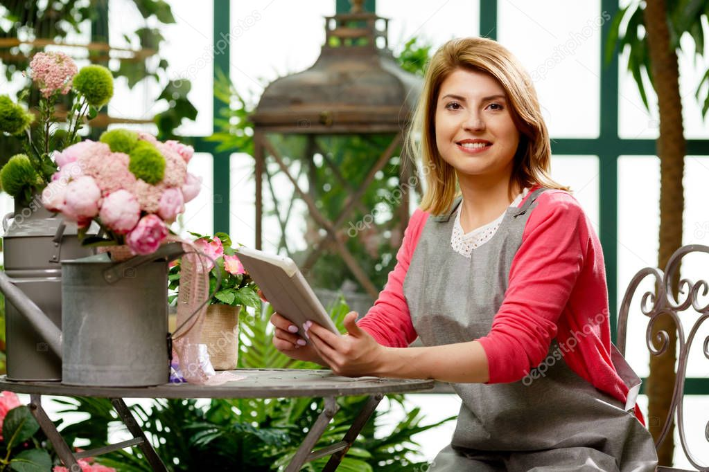 Florist with tablet with flowers