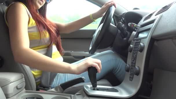 Mladá žena sedí v autě, spusťte motor a jízdy