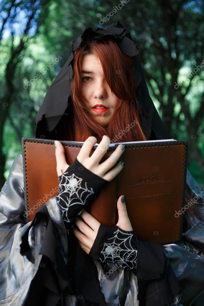 Portrait of witch in cloak with book