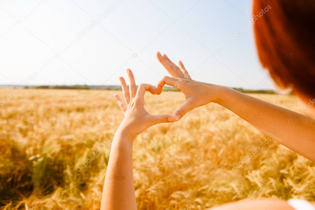 Photo of girl with heart from palms