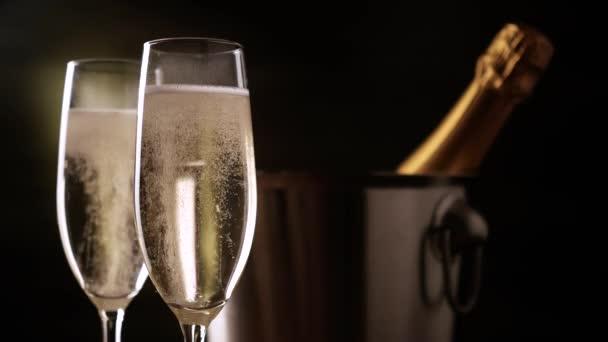 Šampaňské. Dvě flétny s lahví šampaňského v ledové vědro na pozadí.