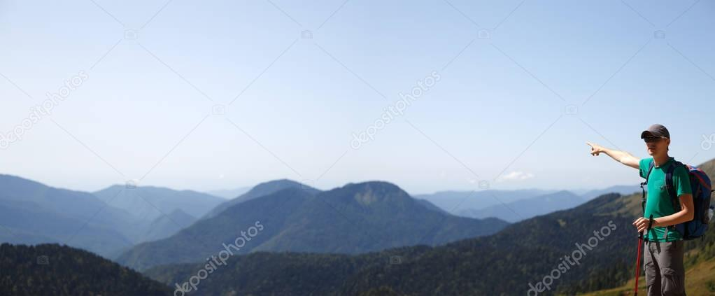 Photo of man pointing to distance background of mountains