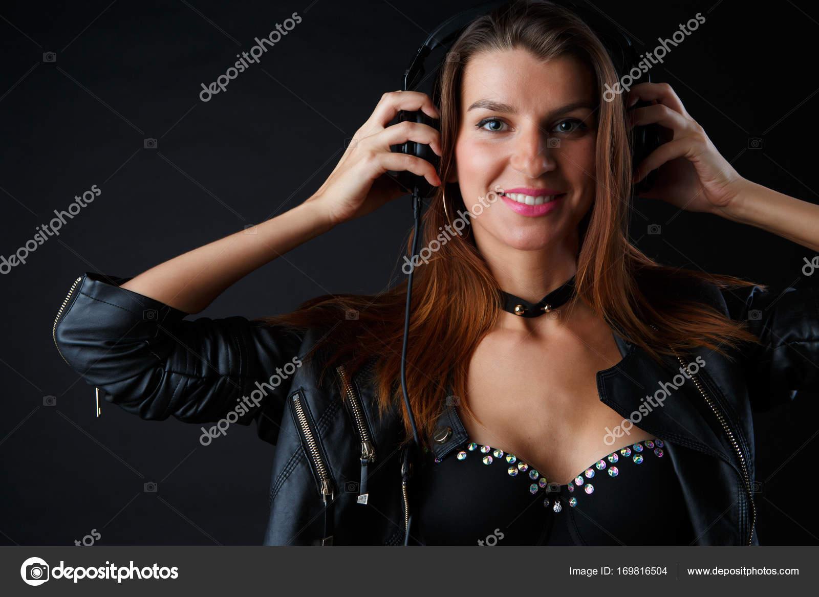Φωτογραφία της νεαρής γυναίκας που φορώντας ακουστικά σε δερμάτινο μπουφάν  και εσώρουχο σε μαύρο φόντο — Εικόνα από logoff abd4dcbc199