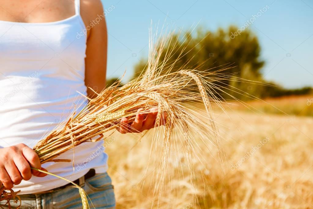 Photo of girl in white T-shirt with spikelets