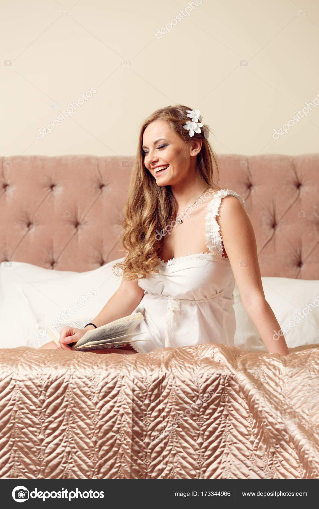 image of happy woman in white negligee sitting on bed — stock photo